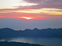 Sunrise over sea, volcanos and lake viewed from the peak of Mount Batur.