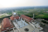 The Great Mosque of Central Java in Semarang, surrounded by rise fields and a marble floor, so shiny that it reflects the building.